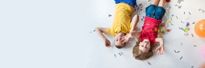 A girl and a boy lay on the white floor and play colorful air balloons on the birthday party top view