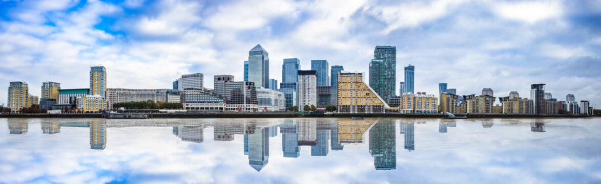 Panorama of Canary Wharf business district with water reflection