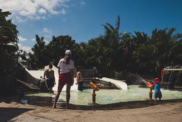 Female lifeguard standing near kids swimming pool.