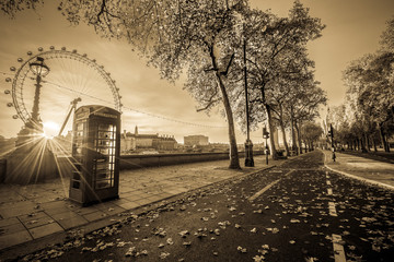 Red telephone booth isolated on black and white street