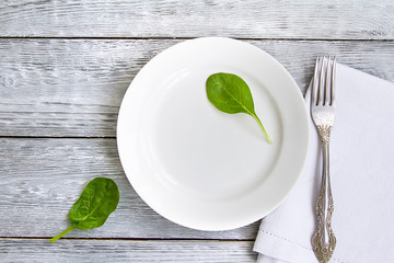white plate with a fork on a wooden table and two leaves of spinach