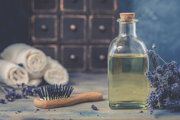 Bottle of natural cosmetic lavender oil, hair and body treatment, with a wooden massage comb