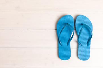 blue flip flops on white wooden background