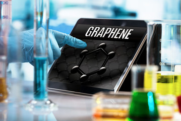 engineer working in the research laboratory with the tablet and symbol graphene in the screen / researcher working in the lab with screen computer and conceptual representation of graphene material