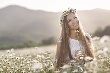 Beautiful girl outdoors with a bouquet of flowers in a field of white daisies,enjoying   nature. Beautiful Model with long hair in white dress having fun on summer Field with blooming flowers