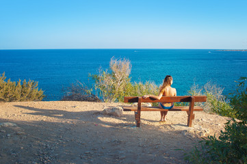 caucassian girl with wet hair sitting on wooden bench