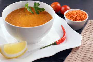 Lentil soup in a plate, next to vegetables and a slice of lemon