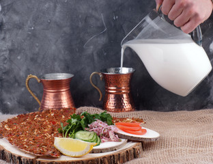 Lunch with Turkish tortilla Lagmajun, a man's hand pours a Turkish national drink ayran in special dishes