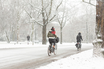 Woman biking in a snowy Amsterdam Vondelpark.