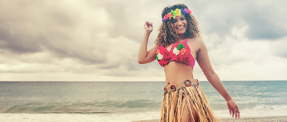 Beautiful and happy hawaiian woman dancing on the beach, letterbox