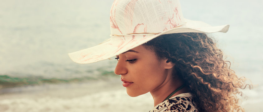 Gorgeous woman portrait deep in thought on the beach, letterbox