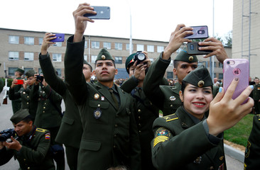 Cadets from Venezuela take pictures during a ceremony of receiving diplomas at the Military Academy of Belarus in Minsk