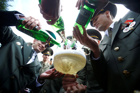 Graduates fill a glass of champagne as they celebrate after receiving diplomas at the Military Academy of Belarus in Minsk