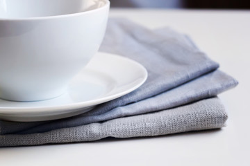 Empty white plate and bowl on a stack of gray napkins on a table.