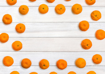 Fresh mandarin oranges on background of white painted wooden planks with space for text. Top view, flat lay