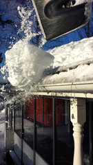 Man shovelling snow from a roof in Sweden