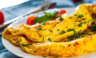 omelette in a white plate on wooden table