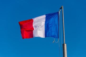 French flag waving against blue sky in Boulogne sur Mer, France.