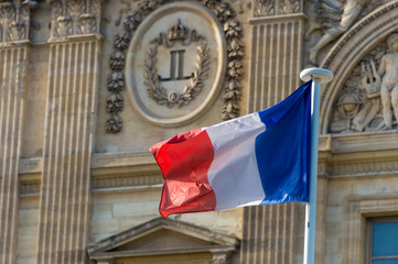 French flag waving in front of the facade of the Louvre Museum in Paris