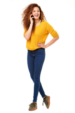 Full body happy woman talking with cellphone against isolated white background