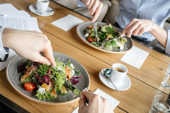 Businesspeople having business lunch at restaurant sitting eating salad close-up