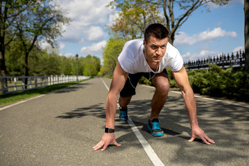 Athletic man is bending to asphalt in crouch start. He is getting ready for running along sunny road in park while feeling very concentrated. Male is wearing smartwatch and using headphones
