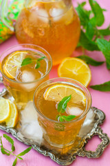 Sweet iced tea with mint, lemon and ice cubes