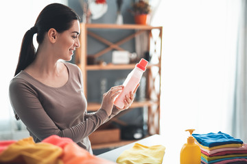 Profile of happy housewife standing at table and holding bottle of detergent in hands. She is reading instructions for use on washing liquid jar. Pile of folded clothes and soap standing aside