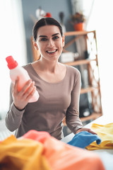 Waist up portrait of content woman holding pink detergent with happy face. She satisfied with using washing liquid to remove stains from dirty clothes