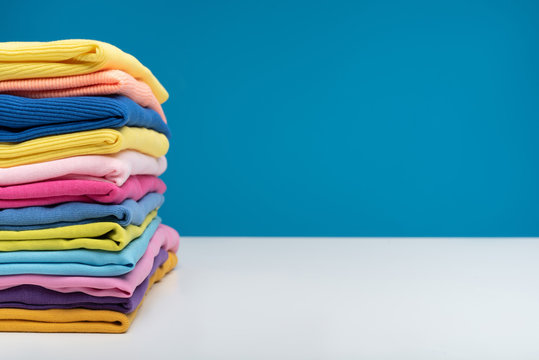 Close up of pile of folded colorful t-shirts after laundry. They are stacked neatly in heap. Copy space in right side