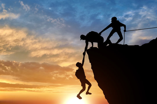 Silhouette of three male climbers rescuing another male climber pulling his arm