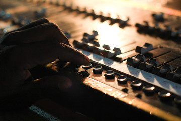 hands operating buttons of light and sound board console at a concert theater