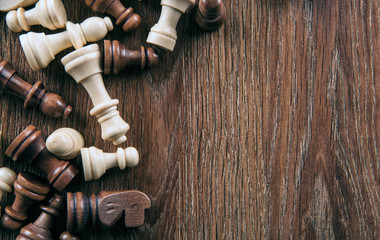 scattered chess pieces on a wooden background