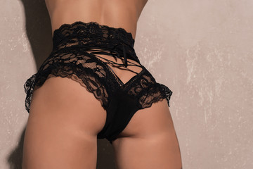 Sexy girl bottom in black erotic lace panties.