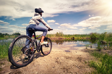 Cyclist stands on the shore of lake under bright sun
