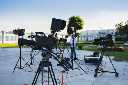 broadcast tv; movie shooting or video production and film, tv crew team with camera, light and audio equipment at outdoor location