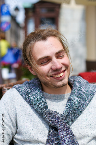 fcf718cc Portrait of handsome smiling man wearing grey sweater. Concept of male  person and fashionable wear style.