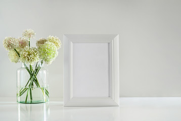 White frame on a table top and garlic flowers bouquet, front view