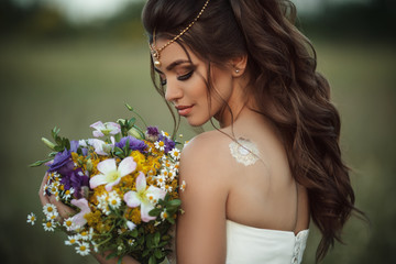 Pretty young bride with bouquet of wildflowers