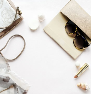 Flat lay set of luxury female clothing and accessories in pastel colors  scarf, bag, schoes, make up  and sunglasses on light background. top view. flat lay.copy space