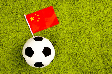 Soccer ball with the flag of China. Football in China. Soccer ball on a green lawn. Flag of China.