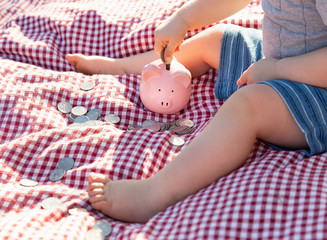 Baby Boy Sitting on Picnic Blanket PUtting Coins in Piggy Bank