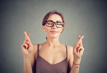 Cute woman in glasses crosses fingers, making a wish