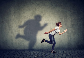 Woman running away from her fat shadow on the wall