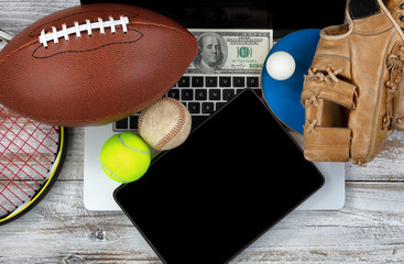 Betting on various sports with computer technology and money in background