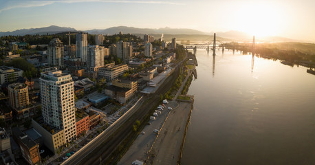 Aerial Panoramic view of Fraser River and Bridges during a vibrant sunrise. Taken in New Westminster, Greater Vancouver, British Columbia, Canada.