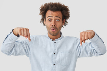 Stunned emotive young curly African American guy indicates down with both fore fingers, advertises something amazing, has surprised expression, isolated over white background. Look at floor!