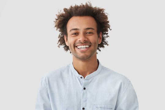 Happy mixed race male student with Afro hairdo shows white teeth, being in good mood after classes as going to have date with female groupmate, stands against white background. Positiveness concept