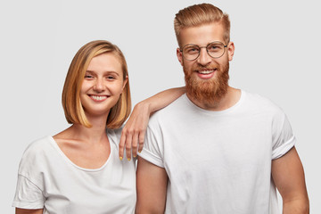Portrait of cheerful young female and male friends have fun together, dressed in casual outfit, isolated over white background. Positive female with bobbed hairstyle and her bearded companion