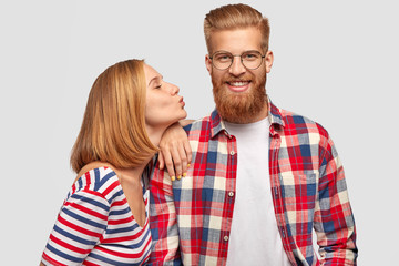 Pleased pretty female with bobbed hairstyle, stands sideways, leans at shoulder of her handsome bearded boyfriend, going to kiss in cheek, expresses love and truthful feeling, isolated on white wall